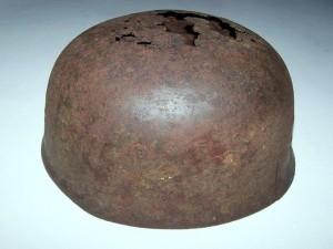 Κράνος Γερμανού αλεξιπτωτιστή το οποίο αγοράστηκε από φίλο και βρέθηκε στη περιοχή των Ροδωπού μέσα σε σπηλιά όπου βρίσκονται ακόμη τα οστά του κατόχου του. Φέρει ακόμη υπολείμματα της αυθεντικής αντιγυαλιστικής επίστρωσης την οποία φέρανε τα κράνη 4 συγκεκριμένων λόχων του Συντάγματος Εφόδου (13ου, 14ου, 15ου και 16ου) που ρίφθησαν τη πρώτη μέρα της Μάχης της Κρήτης στη περιοχή Ταυρωνίτη-Κολυμπαρίου. Η επίστρωση αυτή είναι ένα παχύ, ακανόνιστου πάχους στρώμα πράσινου μπογιά που κάλυπτε το αρχικό γυαλιστερό χρώμα και τα εμβλήματα για λόγους καλύτερης παραλλαγής. Τα κράνη των αλεξιπτωτιστών με αυτή την επίστρωση είναι σήμερα εξαιρετικά σπάνια και το συγκεκριμένο αποτελεί το μοναδικό σωζόμενο του είδους σε ολόκληρη τη Κρήτη σήμερα.