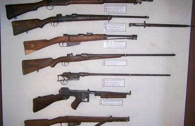 Από πάνω προς τα κάτω βρετανικό τουφέκι Enfield P14, ελληνικό τουφέκι Mauser FN 1930 με τη ξιφολόγχη του, ιταλικό τουφέκι Mannlicher Carcano Μ1891, τούρκικο τουφέκι Mauser M1903, ελληνικό τουφέκι Mannlicher Shoenauer M1903, αμερικάνικο υποπολυβόλο Thomson M1928 και ξύλα ιταλικού τυφεκίου Mannlicher Carcano Μ1938.