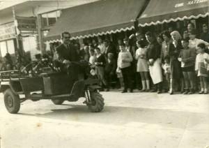 """Η αποδοχή του κόσμου για τα νέα τότε μηχανήματα """"Μινώταυρος"""" αποτέλεσε κοινωνικό φαινόμενο. Παραπάνω, εικόνες από παρέλαση με τρίκυκλα και συρόμενα βαγόνια σε κεντρικό δρόμο κωμόπολης της Κρήτης με τον κόσμο να παρακολουθεί! (Αρκαλοχώρι)"""