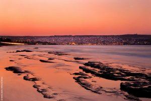 Από τις πιο ιδιαίτερες παραλίες της Σητείας, η ακτή της Πετράς προσφέρει απόκοσμες εικόνες, με τα βράχια της να εξαϋλώνονται στο φως του σούρουπου. Στο βάθος διακρίνονται τα φώτα της Σητείας