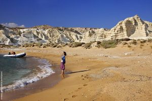 Ερημική αμμουδιά με ριγωτά βράχια -χαρακτηριστικό τοπίο από τη Λευκή ή Κουφονήσι